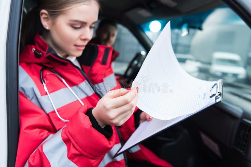 vrouwelijke paramedicuszitting in ziekenwagen en het kijken royalty-vrije stock foto's