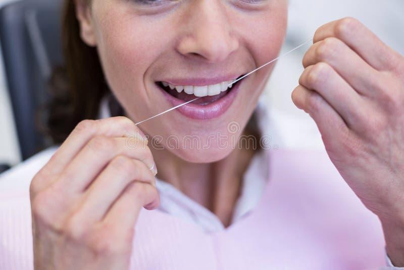 Vrouwelijke patiënt die haar tanden flossing royalty-vrije stock afbeeldingen