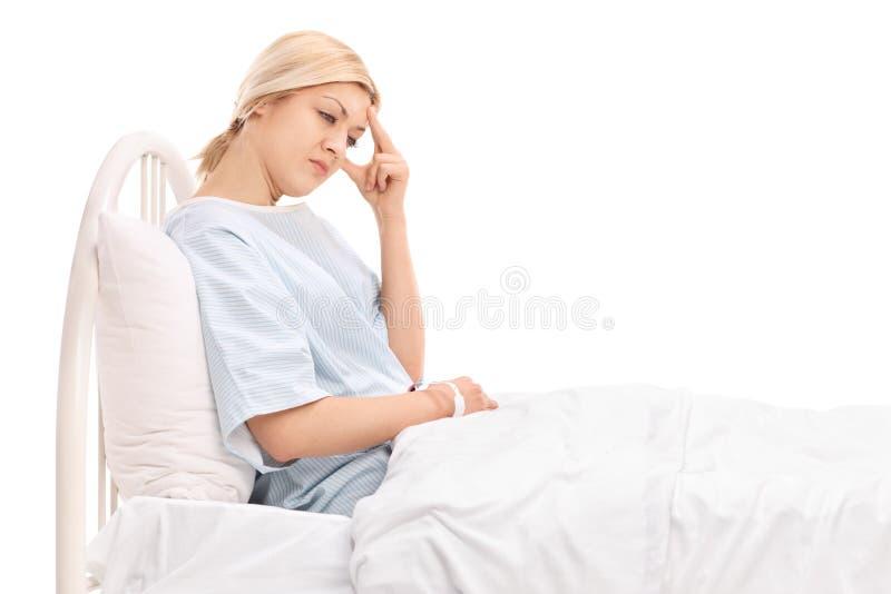 Vrouwelijke patiënt die in het ziekenhuis liggen en een hoofdpijn hebben stock foto