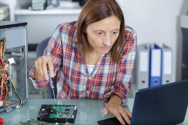 Vrouwelijke PC-technicus die leerprogramma voor het bevestigen van computer bekijken stock afbeelding