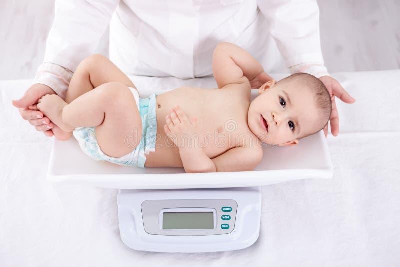 Vrouwelijke pediater wegende baby in bureau stock afbeeldingen