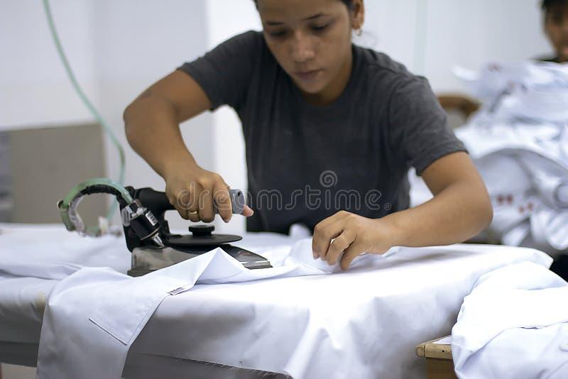 Vrouwelijke Peruviaanse arbeider het strijken kleren stock afbeeldingen