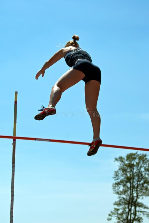 Vrouwelijke pool vaulter in mid-air stock fotografie