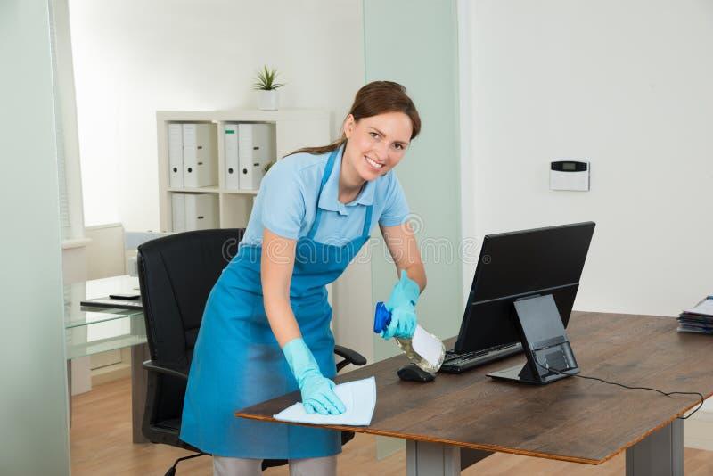 Vrouwelijke Portier Cleaning Desk stock foto