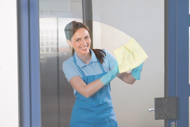 Vrouwelijke Portier Cleaning Glass stock afbeeldingen