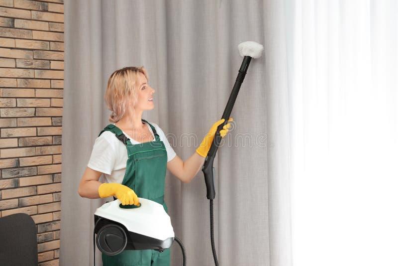 Vrouwelijke portier die stof verwijderen uit gordijn met stoomreinigingsmachine stock afbeelding