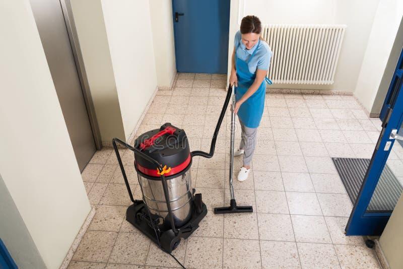 Vrouwelijke portier schoonmakende vloer stock foto's