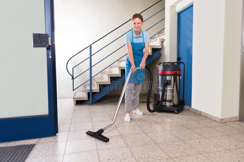 Vrouwelijke portier schoonmakende vloer stock fotografie