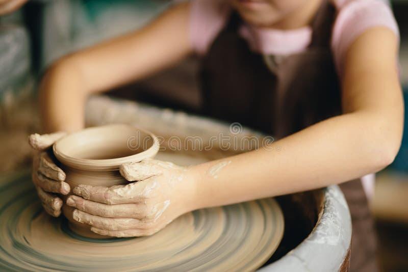 Vrouwelijke pottenbakker die bij het werpen van wiel bij studio werken Kleiworkshop royalty-vrije stock foto's