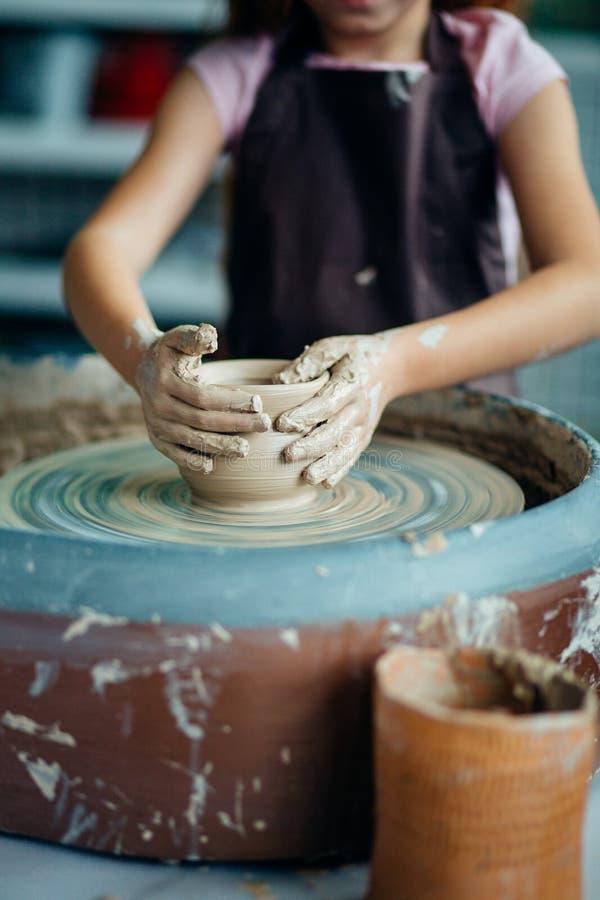 Vrouwelijke pottenbakker die bij het werpen van wiel bij studio werken Kleiworkshop royalty-vrije stock afbeelding
