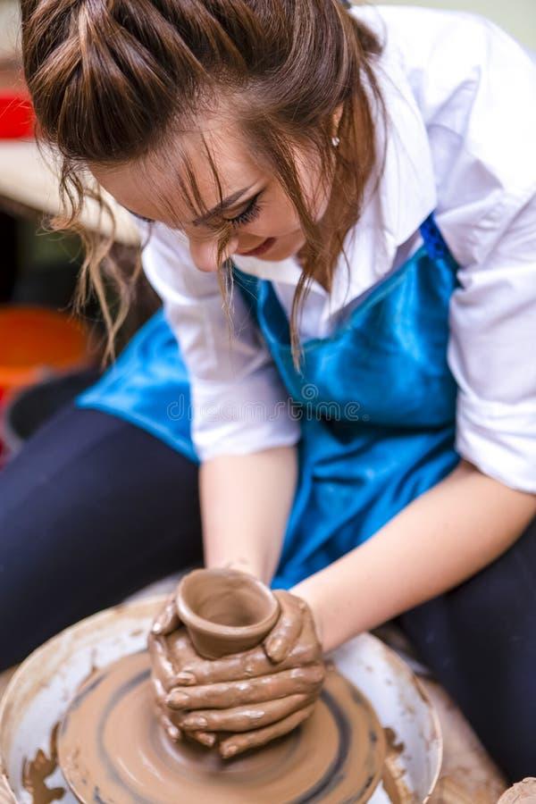 Vrouwelijke Pottenbakker die met Clay Lump aan het Wiel van de Pottenbakker in Workshop werken royalty-vrije stock fotografie