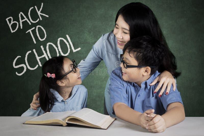 Vrouwelijke privé-leraar met haar student in de klasse stock foto