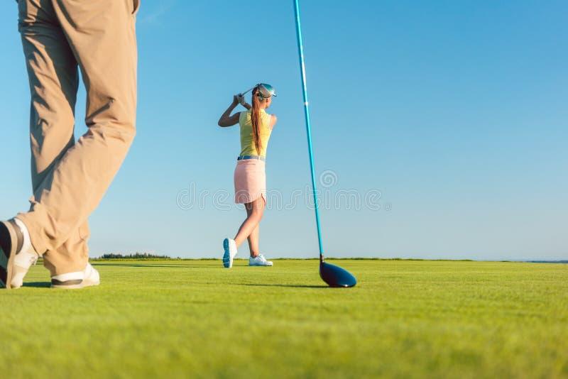 Vrouwelijke professionele golfspeler die een lang schot raken tijdens een opwindend spel stock foto's