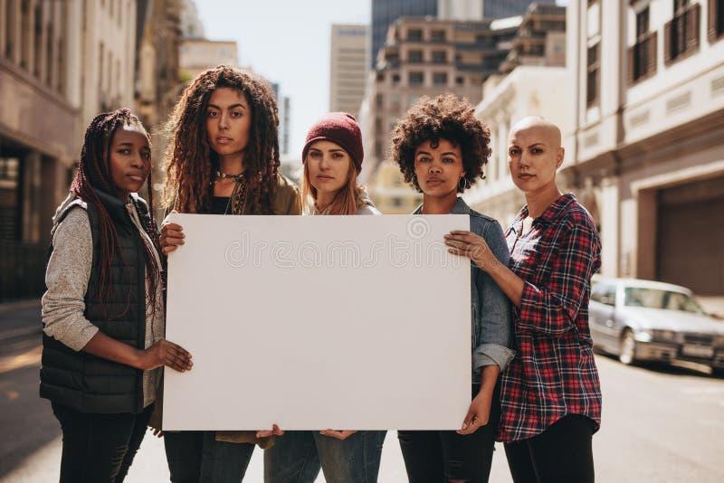 Vrouwelijke protesteerders met lege banner stock afbeelding