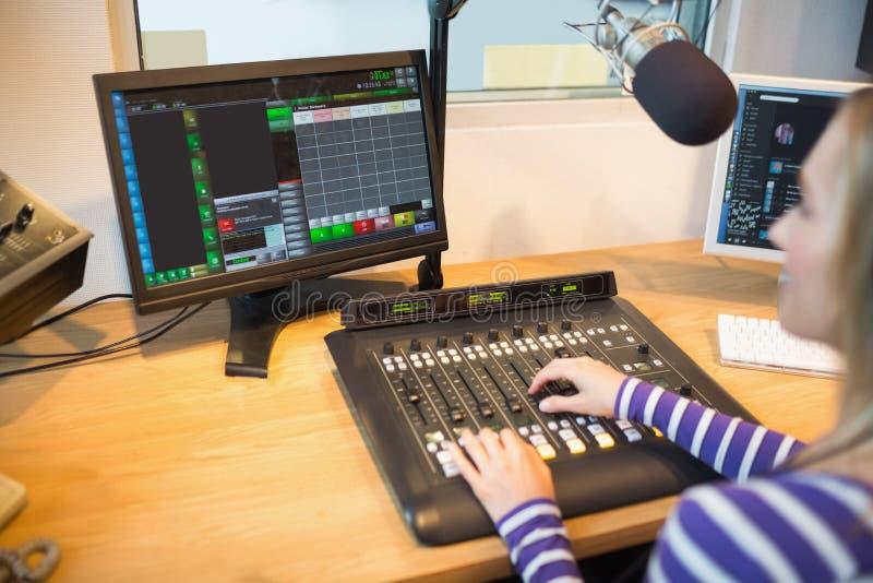 Vrouwelijke radiogastheer voor het scherm die correcte mixer in werking stellen stock fotografie