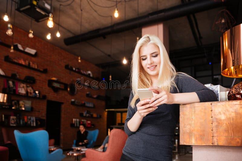 Vrouwelijke receptionnist van schoonheidssalon met smartphone stock afbeeldingen