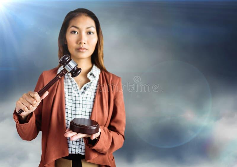 Vrouwelijke rechter met hamer tegen blauwe bewolkte hemel met gloed stock afbeeldingen