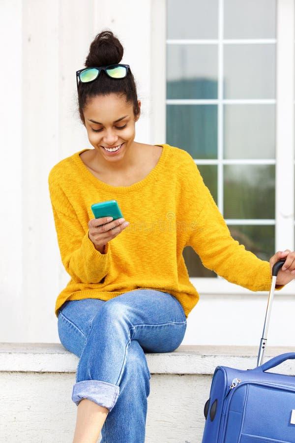Vrouwelijke reiziger die mobiele telefoon met behulp van stock foto