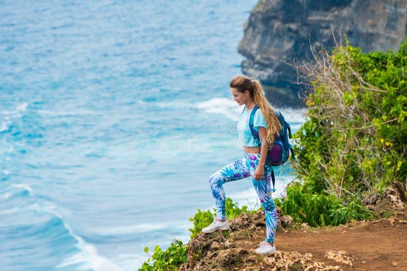 Vrouwelijke reiziger met een rugzak die zich op de rand van een klip bevinden en van de mening van de oceaan genieten Bali, Indon stock afbeeldingen