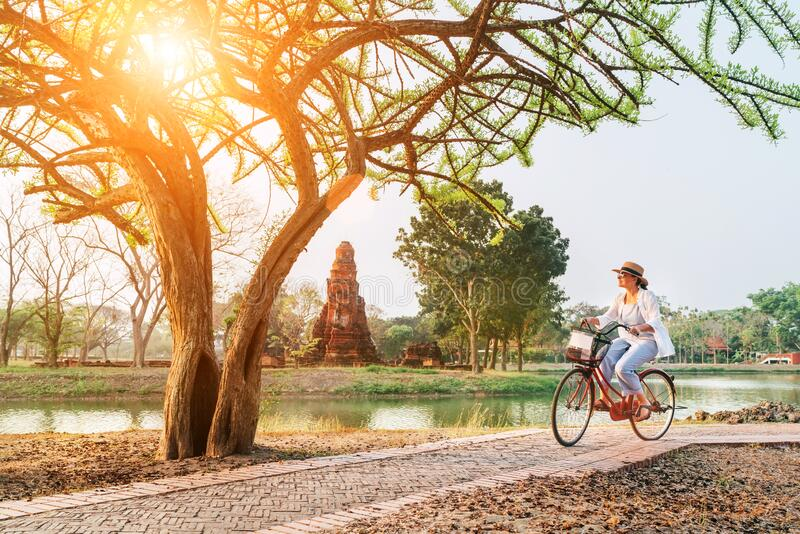 Vrouwelijke reizigers muurden lichte zomerkleding en hoorden vroege ochtendfietswandeling in het historische park Ayutthaya, Thai royalty-vrije stock afbeelding