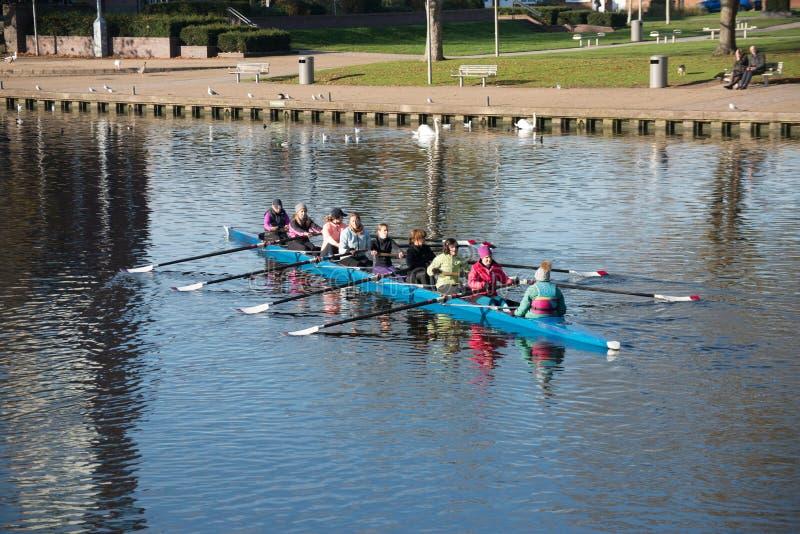 vrouwelijke roeiers die op rivier met bank op achtergrond opleiden royalty-vrije stock foto's