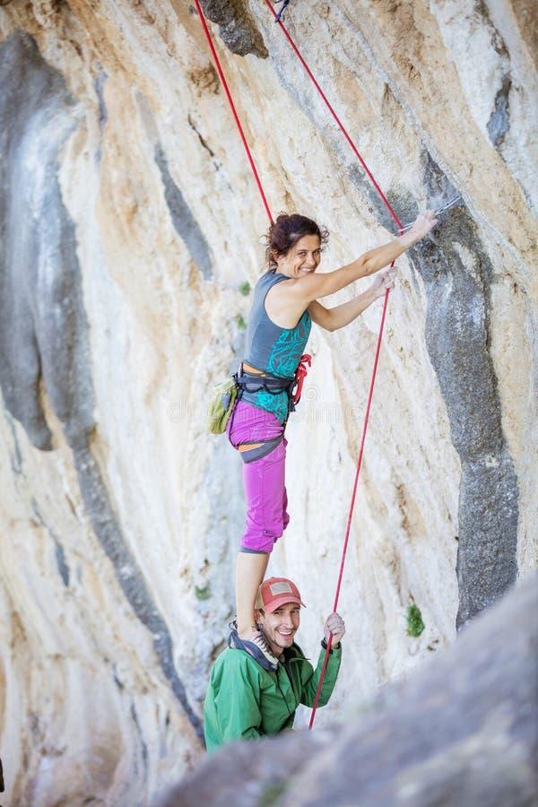 Vrouwelijke rotsklimmer die zich op schouders van haar partner bevinden beginnen uitdagingsroute te beklimmen stock afbeeldingen