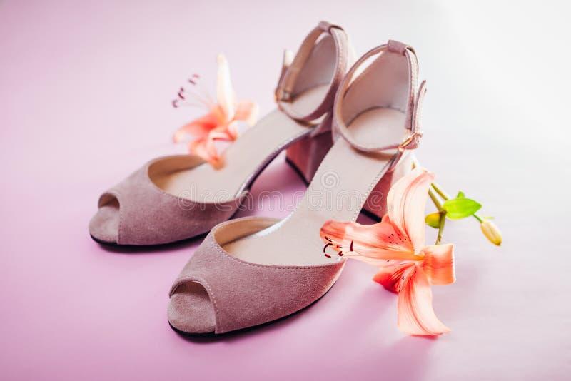 Vrouwelijke roze schoenen met leliebloemen op roze achtergrond Manier royalty-vrije stock afbeelding