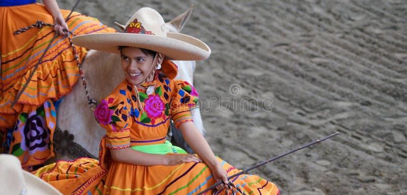 Vrouwelijke ruiter in oranje kleding met bloemen stock fotografie