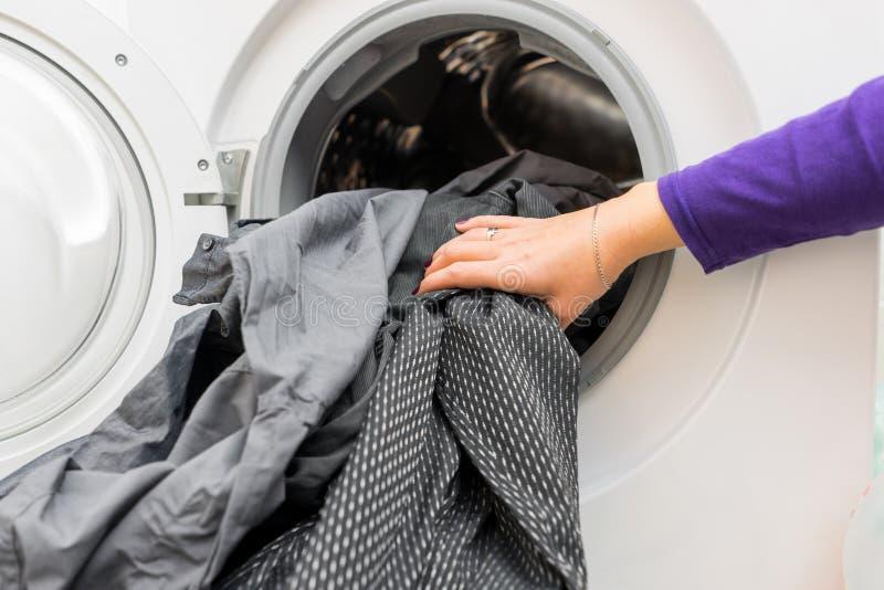 Vrouwelijke 's-handen die vuile kleren zetten in wasmachine stock foto