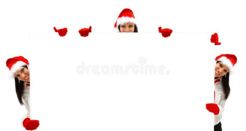 Vrouwelijke Santas over een aanplakbord royalty-vrije stock afbeelding