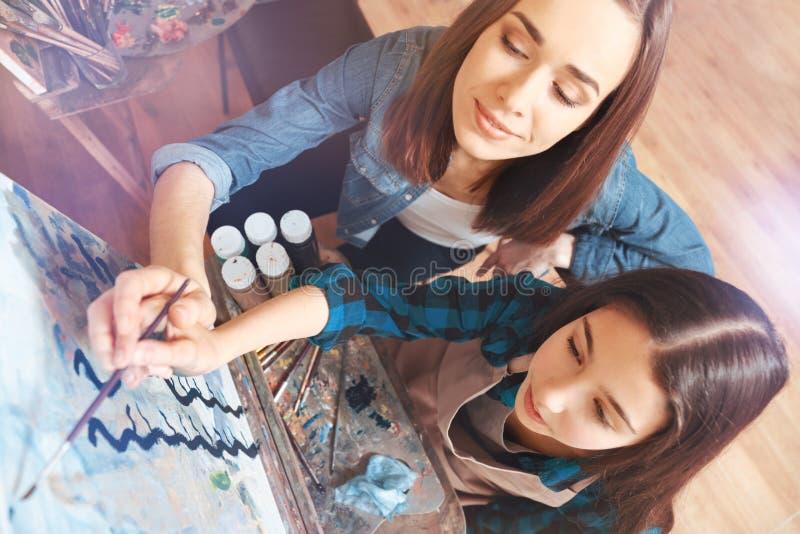 Vrouwelijke schilder die meisje met het schilderen helpen stock foto