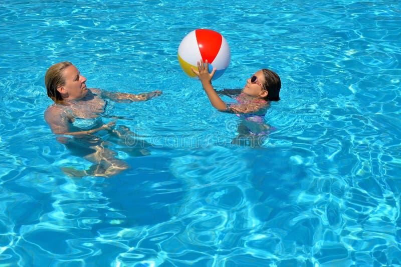 Vrouwelijke schoonheid ontspannen in zwembad met haar dochter stock foto