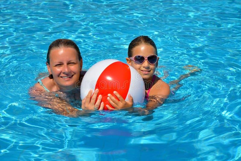 Vrouwelijke schoonheid ontspannen in zwembad met haar dochter royalty-vrije stock afbeelding