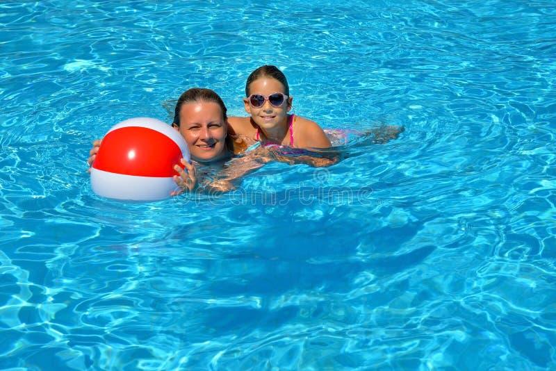 Vrouwelijke schoonheid ontspannen in zwembad met haar dochter royalty-vrije stock foto's