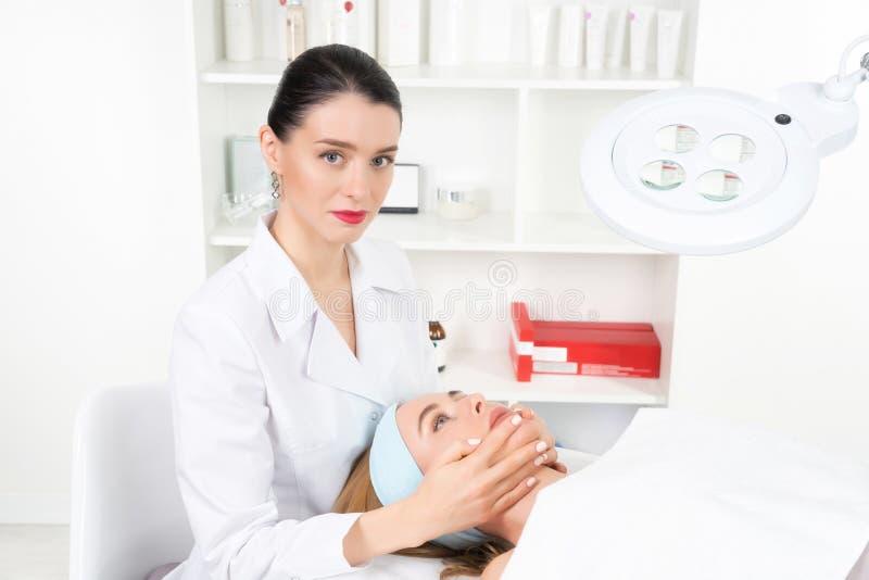 Vrouwelijke schoonheidsspecialist arts met patiënt in wellnesscentrum E royalty-vrije stock afbeelding