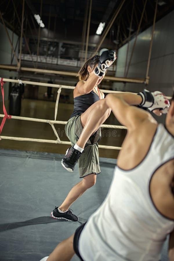 Vrouwelijke schopbokser het praktizeren aanval stock foto's