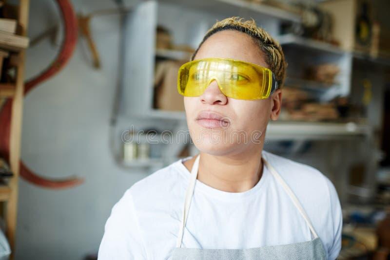 Vrouwelijke schrijnwerker in veiligheidsbeschermende brillen stock afbeeldingen
