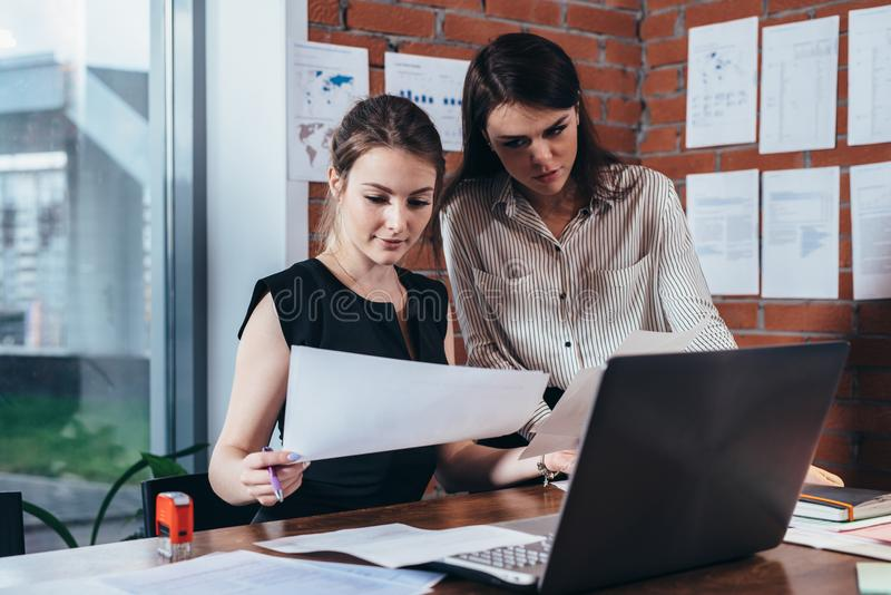 Vrouwelijke secretaresse die betroffen terwijl haar chef- het controleren documentzitting bureau in modern bureau bekijken royalty-vrije stock foto's