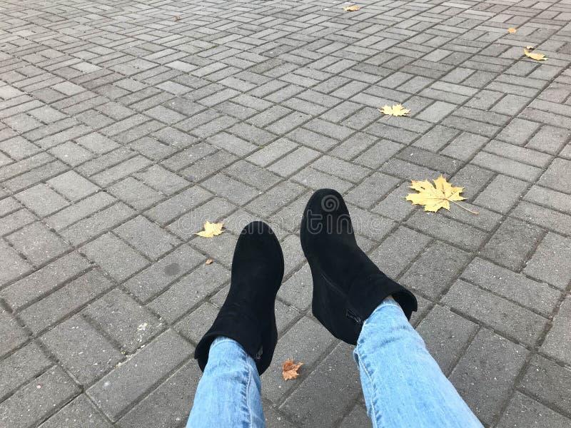 Vrouwelijke slanke benen in jeans en laarzen, schoenen tegen een achtergrond van grijze steen concrete het bedekken plakken en de royalty-vrije stock afbeelding