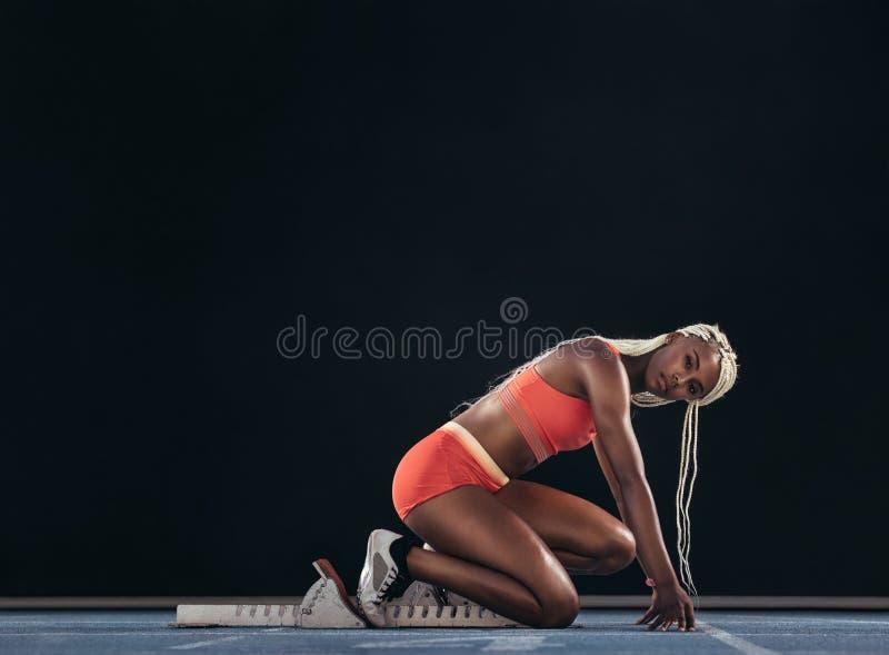 Vrouwelijke sprinter bij de beginlijn die een standpunt betreffende lopend t innemen stock fotografie