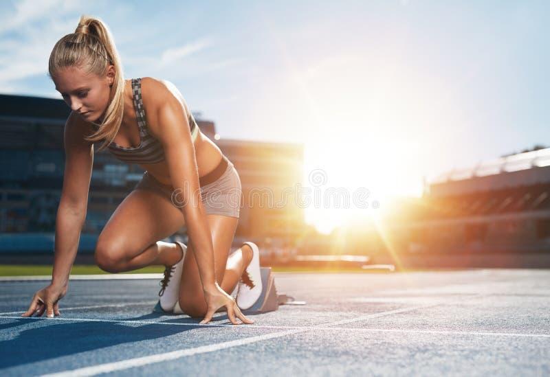 Vrouwelijke sprinter in spoorstartblokken stock foto's