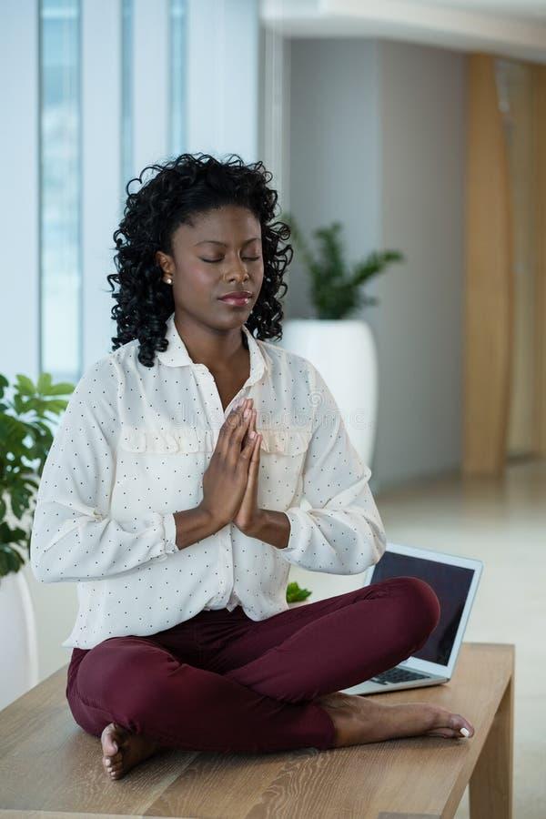 Vrouwelijke stafmedewerker die op bureau mediteren stock afbeeldingen