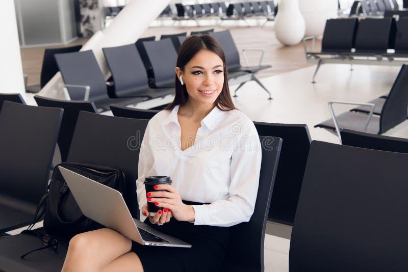 Vrouwelijke stafmedewerker met koffer in het werk verwante zakenreis die op haar vlucht in een luchthaven wachten stock afbeeldingen