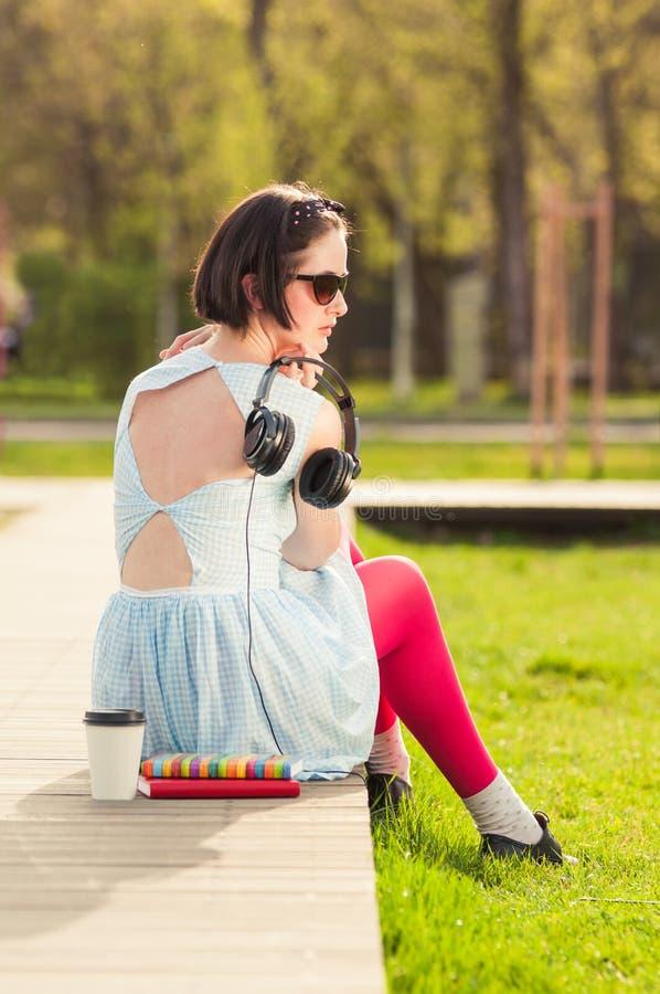 Vrouwelijke stellende buitenkant in park met hoofdtelefoons, boeken en koffie stock fotografie