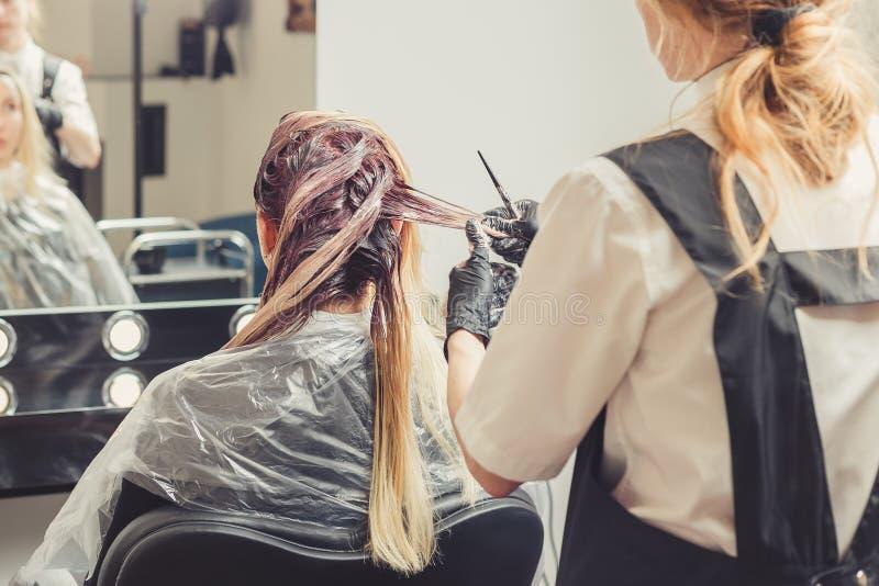 Vrouwelijke stilist die een kleurstof toepassen op het cliëntenhaar stock foto