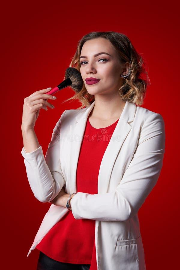 Vrouwelijke stilist die zich met make-upborstel bevinden over rode achtergrond royalty-vrije stock foto