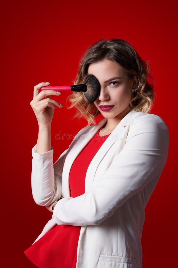 Vrouwelijke stilist die zich met make-upborstel bevinden over rode achtergrond royalty-vrije stock afbeeldingen