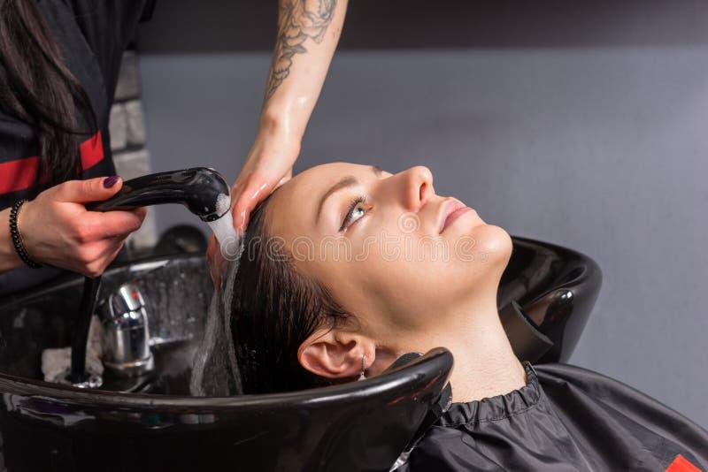 Vrouwelijke stilistwassen van de shampoo van jonge vrouw in was stock foto
