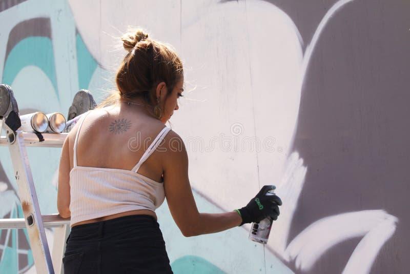 Vrouwelijke straatkunstenaar die kleurrijke graffiti op muur schilderen - Modern kunstconcept met het stedelijke meisje schildere stock fotografie
