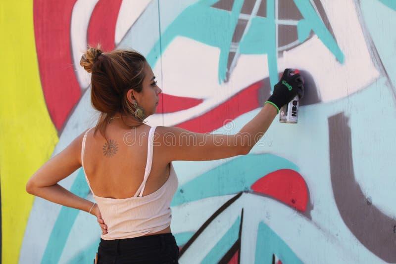 Vrouwelijke straatkunstenaar die kleurrijke graffiti op muur schilderen - Modern kunstconcept met het stedelijke meisje schildere stock afbeelding